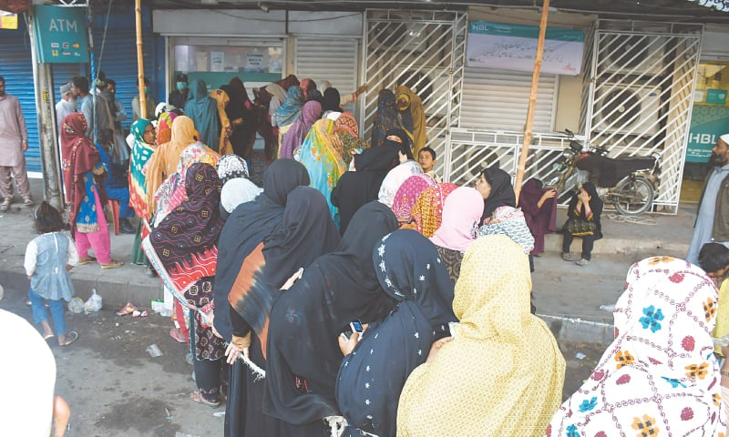 SOPs go out the window as women queue up outside a bank in Abbas Town for Ehsaas payments on Friday.—Faysal Mujeeb / White Star