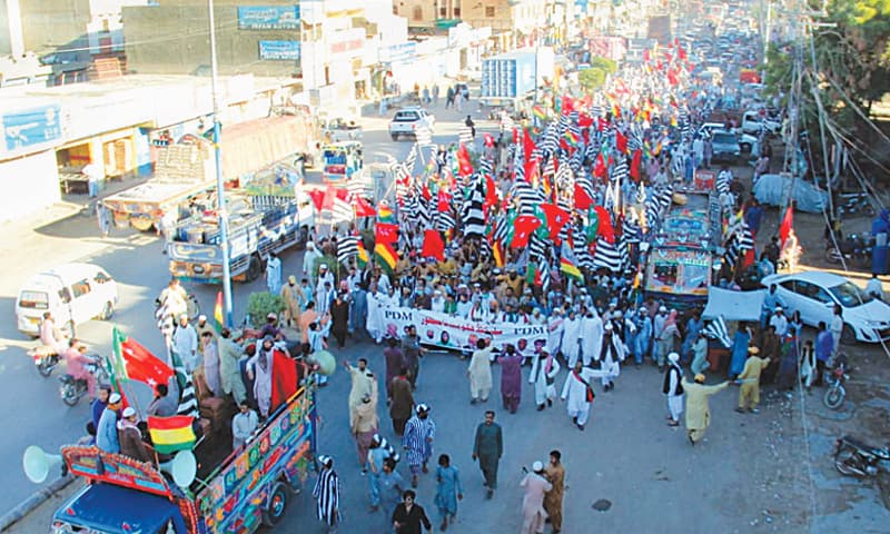 HUB: Activists and supporters of the Pakistan Democratic Movement march on a road on Friday. — PPI