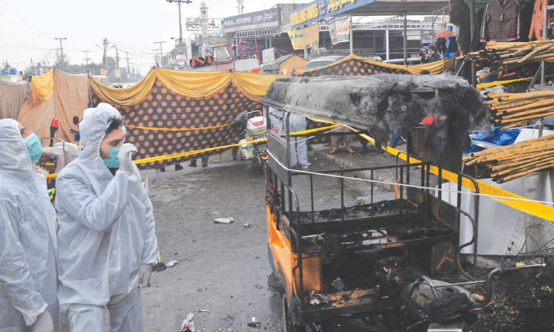 POLICE investigators collect evidence from the blast site in the Pirwadhai area on Friday.—Tanveer Shahzad/White Star