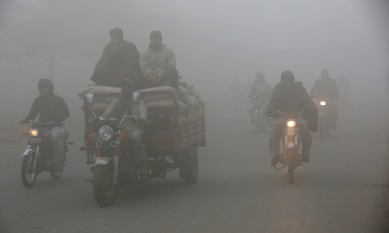 Motorcyclists drive along a road in heavy fog in Lahore on Friday. — AP