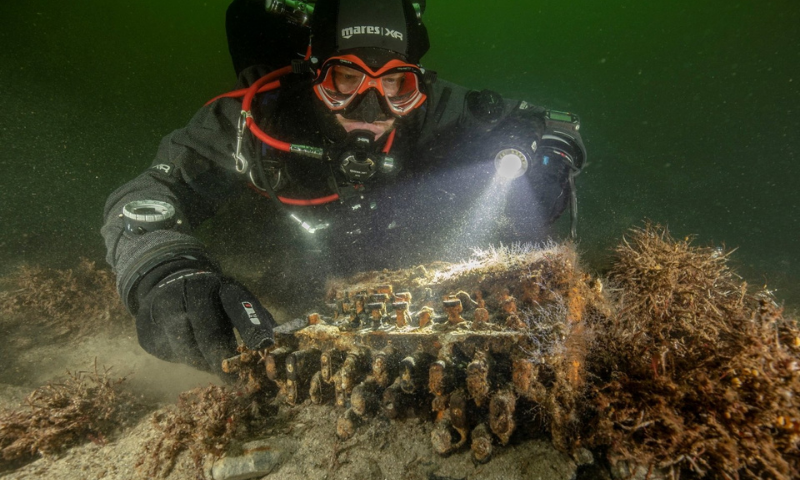 Diver and underwater archaeologist Florian Huber touches a rare Enigma cipher machine used by the Nazi military during World War II, in Gelting Bay near Flensburg, Germany on Nov 11. — Reuters/File