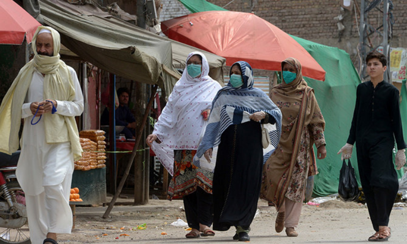 In this file photo, women wearing facemasks walk on a street. — AFP