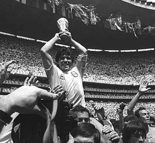 Argentine star Diego Maradona holds up the 1986 FIFA World Cup trophy as he is carried off the field | Reuters