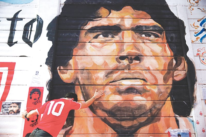 A boy touches a mural of Maradona outside the stadium of Argentinos Juniors football club in Buenos Aires | AP
