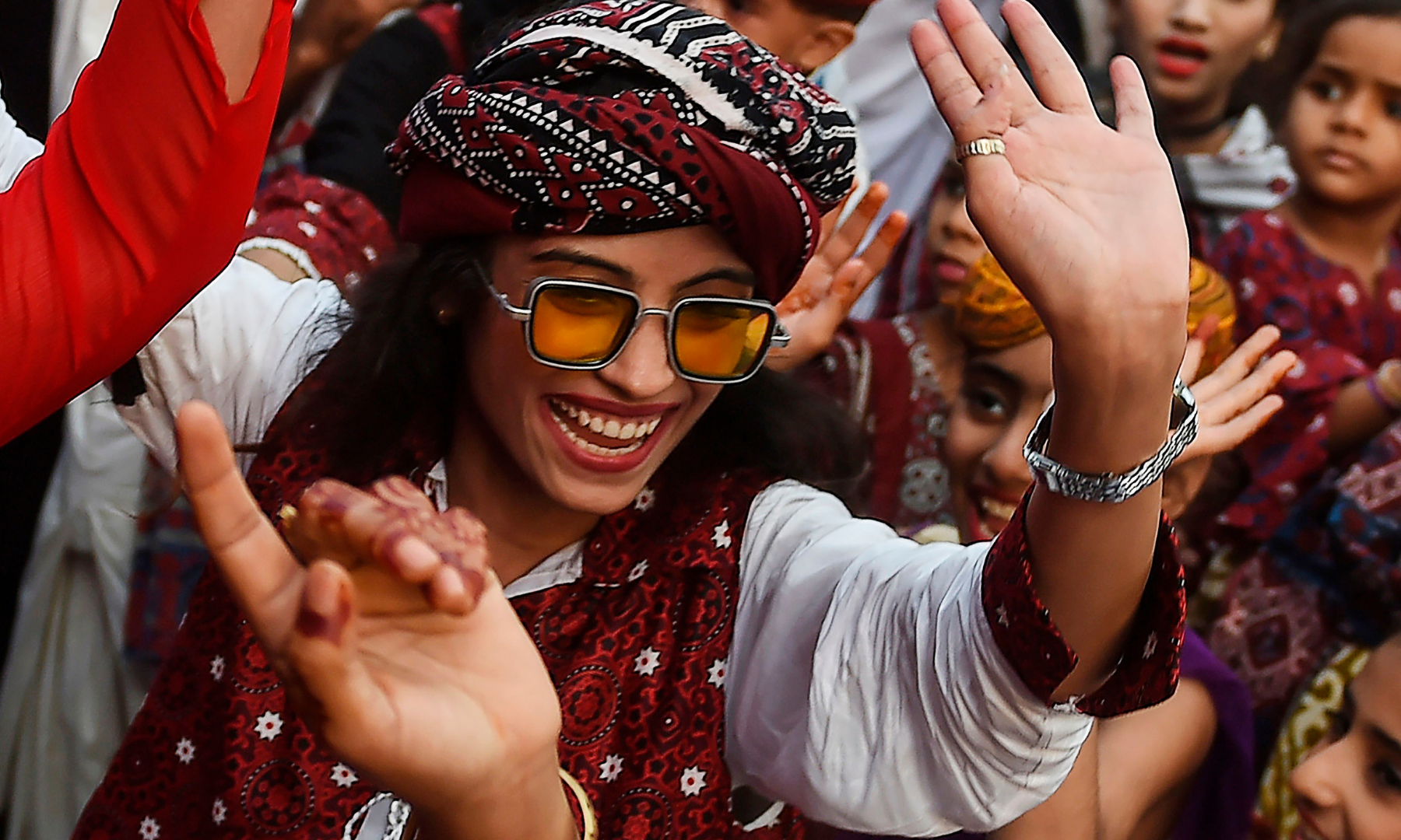 A woman, wearing a traditional dress, dances as she celebrates during the Sindh Culture Day in Pakistan's port city of Karachi on December 6. — AFP