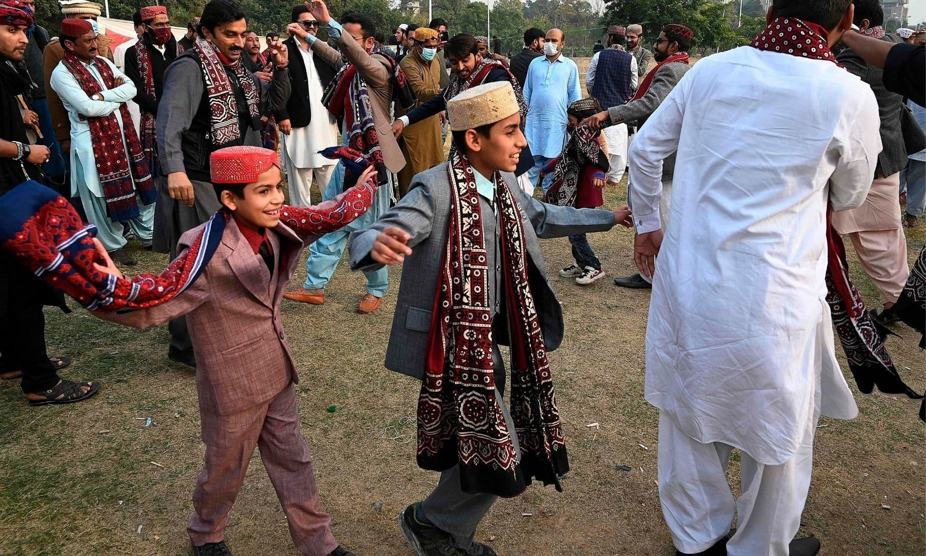 People wearing traditional dresses dance to celebrate the Sindh Culture Day in Islamabad. — AFP