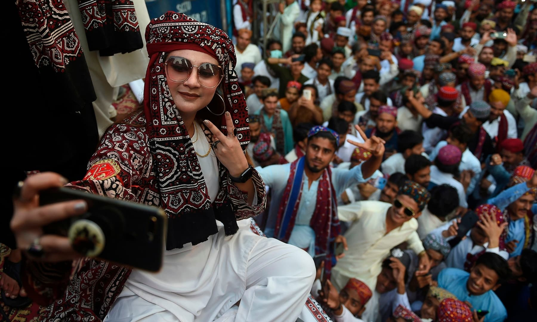 A woman wearing traditional a dress takes a selfie picture as she celebrates during Sindh Culture Day in Karachi. — AFP