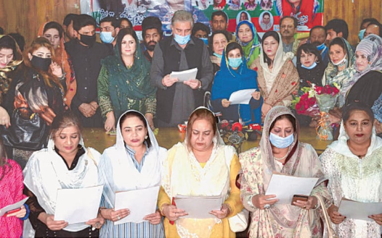 Foreign Minister Shah Mehmood Qureshi administers the oath to members of the PTI's women wing of Multan district and minority members during a ceremony on Sunday.—INP