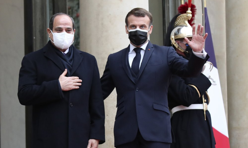 French President Emmanuel Macron, right, and Egyptian President Abdel-Fattah el-Siss gesture upon el-Sissi arrival at the Elysee palace on Monday. — AP