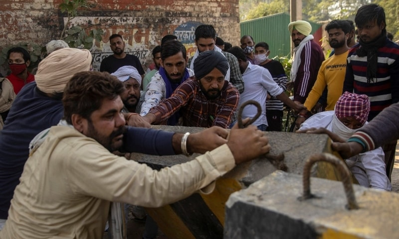 Farmers remove police barricades to reach a protest site during a nationwide strike against the newly passed farm bills at Singhu border near Delhi on December 8. — Reuters