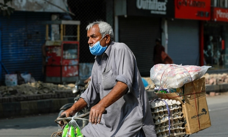 A man wears protective mask as he rides a bicycle loaded with supplies amid the outbreak of the coronavirus in Karachi on November 16. — Reuters
