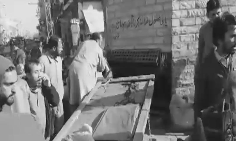Residents gather at the site of an explosion near Rawalpindi's Ganj Mandi police station. — DawnNewsTV
