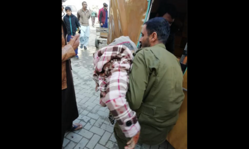 An injured person is being taken to a hospital by a resident after an explosion at Rawalpindi's Ganj Mandi police station. — DawnNewsTV