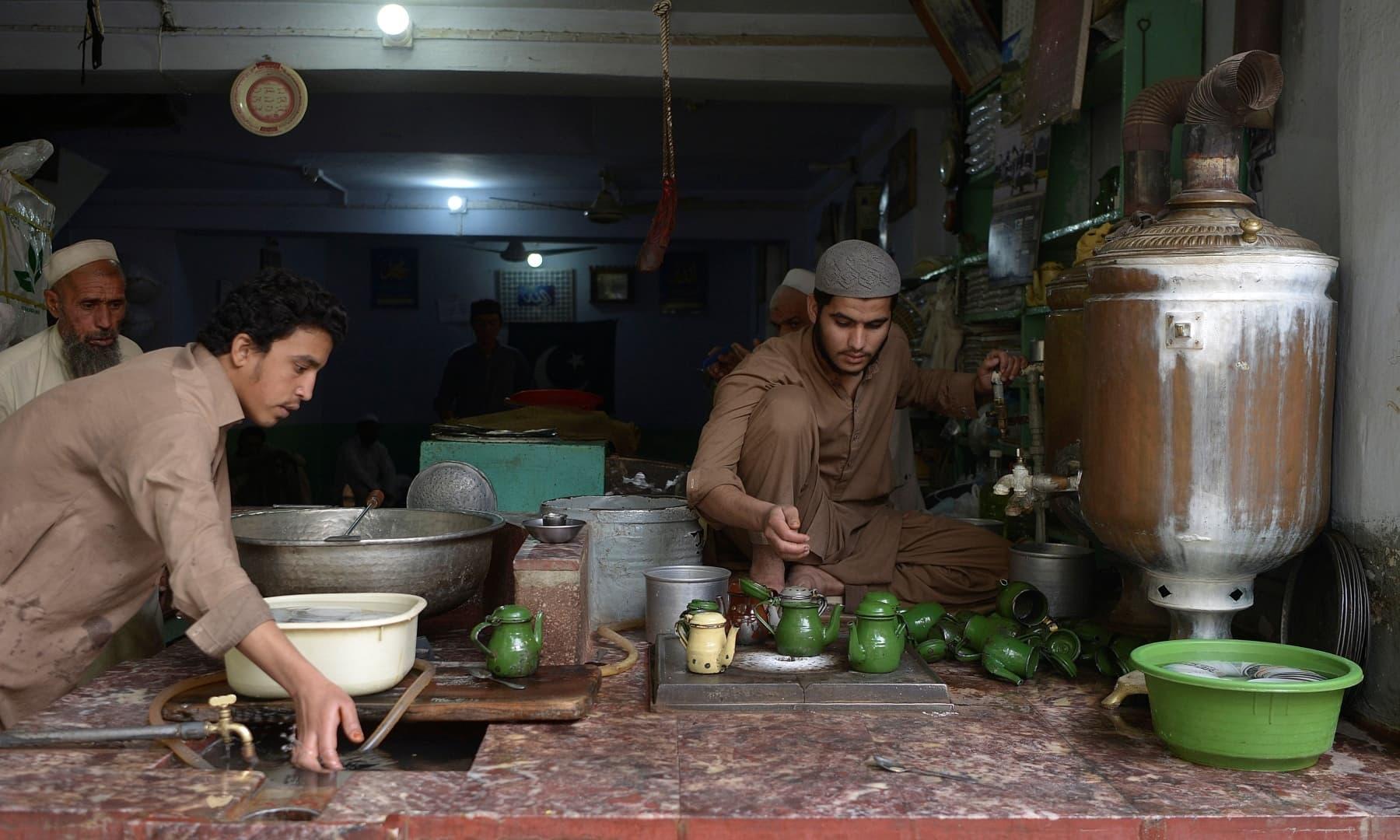 "A man prepares traditional tea for customers at the Qissa Khawani or ""storytellers bazaar"" in Peshawar. — AFP"