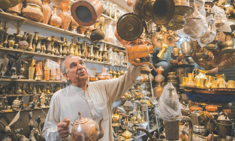 Khwaja Safar Ali arranges items in his antiques shop.—AFP