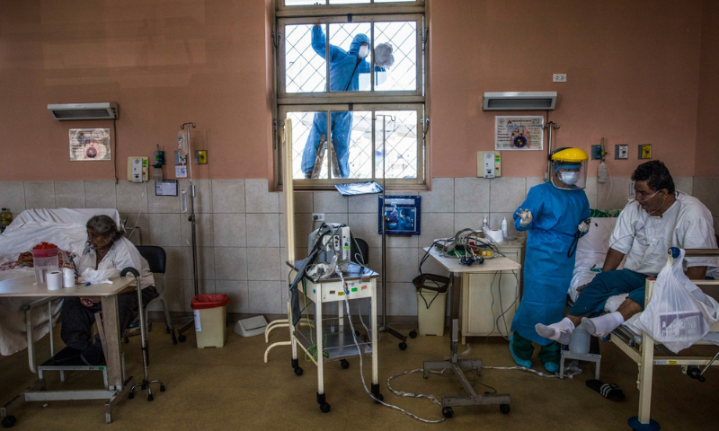 A worker wearing protective gear cleans a window as a nurse tends to a patient inside the intensive care unit for people infected with the coronavirus at the 2 de Mayo Hospital in Lima, Peru, on April 17. — AP