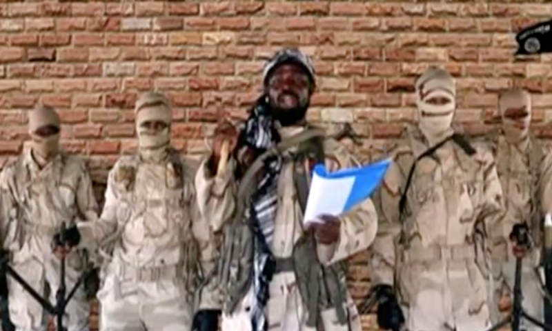 The leader of one of the Boko Haram group's factions, Abubakar Shekau speaks in front of guards in an unknown location in Nigeria in this still image taken from an undated video. — AFP/File