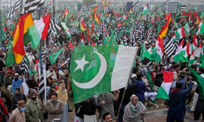 Supporters of the Pakistan Democratic Movement wave flags as they listen to the speeches of their leaders during the Dec 13 rally in Lahore. — Reuters/File