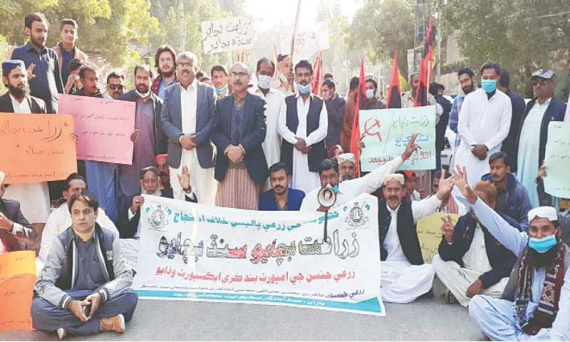 GROWERS hold a demonstration in Hyderabad on Friday against import of onion and tomatoes.—Dawn