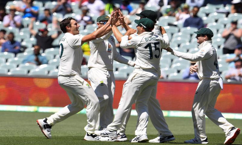 Australia's Pat Cummins (L) celebrates with teammates after dismissing India's captain Virat Kohli in Adelaide on December 19. — AFP