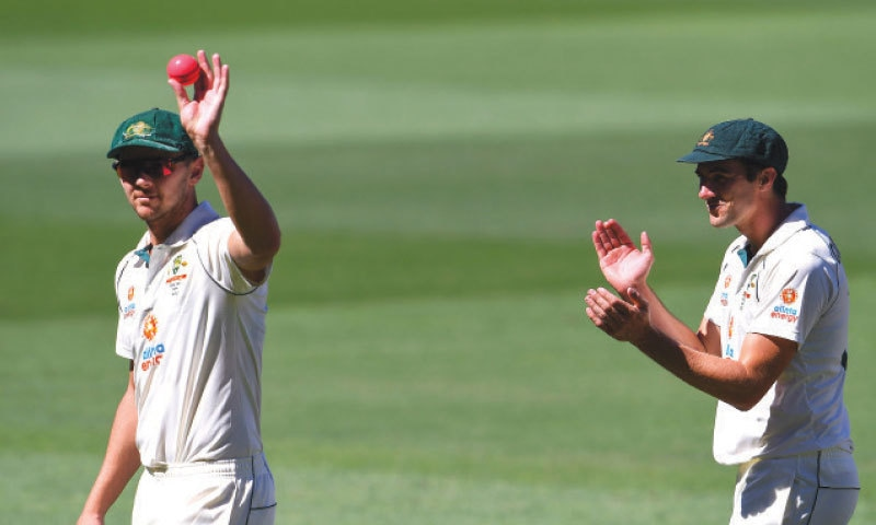 JOSH Hazlewood (L) is applauded by fellow paceman Pat Cummins after taking five  wickets.—AFP