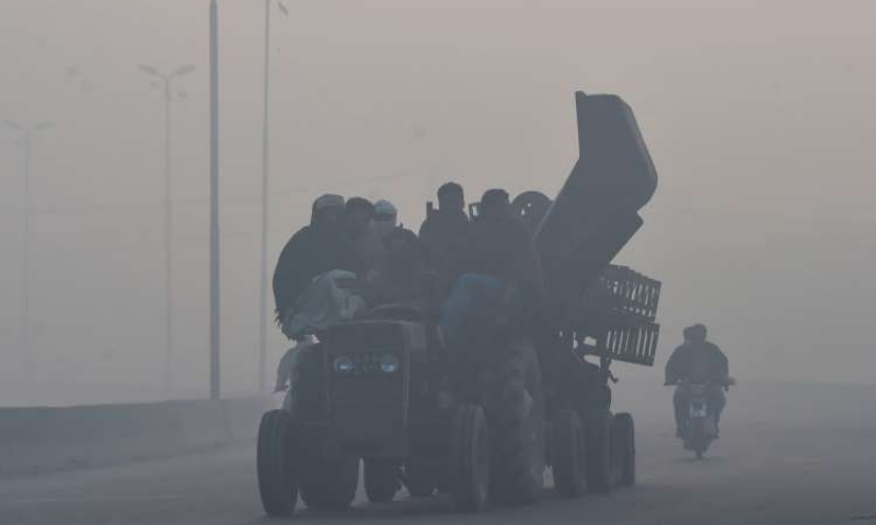 Labourers ride on a tractor along a street amid heavy smoggy conditions in Lahore on December 7. — AFP/File