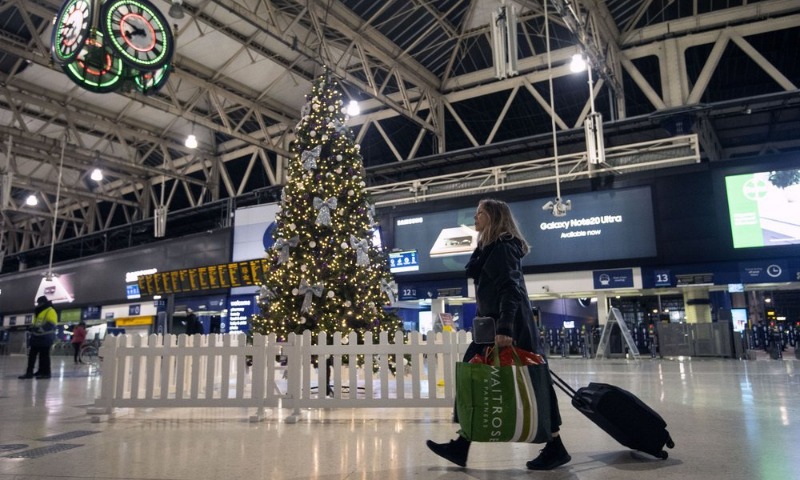 A woman pulls a suitcase past the Christmas tree on the concourse of Waterloo Station in central London on Sunday. — AP