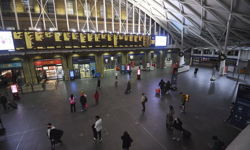 Travellers wait for trains on the concourse at King's Cross station in central London on Sunday. — AP