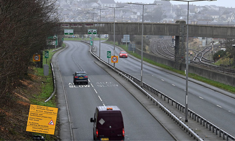 Vehicles are driven past a road sign warning motorists to be prepared from delays once the Brexit transition period ends, as they travel towards Holyhead Port in Holyhead, north wales on December 21. — AFP