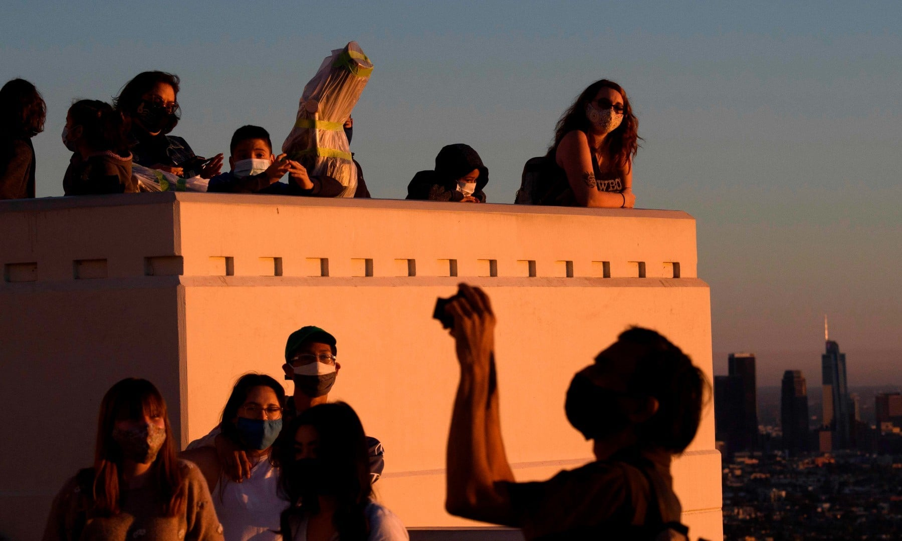 People wearing face masks watch the sunset as they wait to see the planets Jupiter and Saturn during the great conjunction at the Griffith Observatory on Dec 21. —  AFP