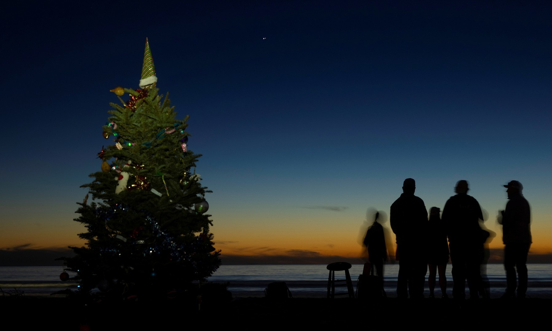 Groups of people gather near a Christmas tree on the beach as they watch the celestial phenomenon of the planets Jupiter and Saturn align in the sky at Cardiff State Beach on Dec 21. — Reuters