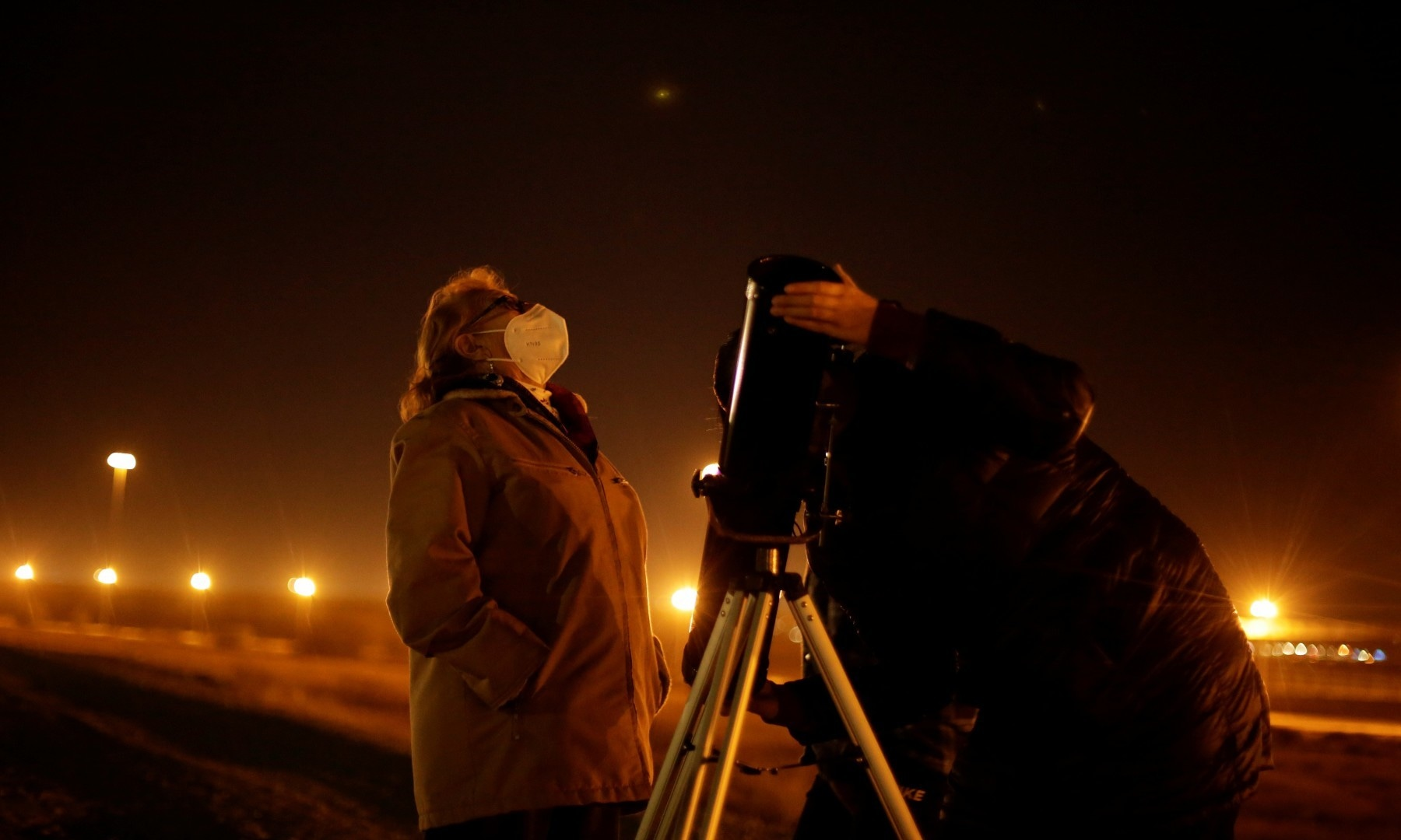 Members of the Mota Velazco family use a telescope to view Jupiter and Saturn during a planetary conjunction in Ciudad Juarez on Dec 21. — Reuters