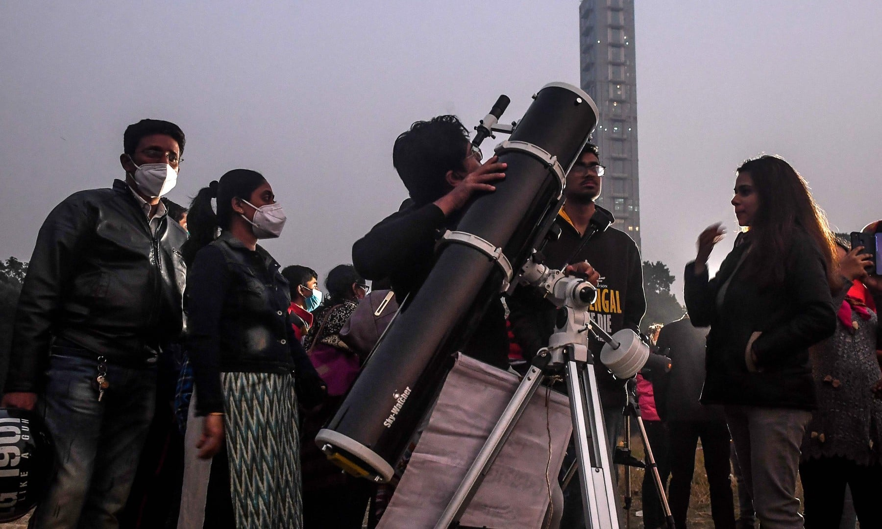 People stand in a queue to see a 'great conjunction' of Jupiter and Saturn at the Maidan area in Kolkata on December 21. —  AFP