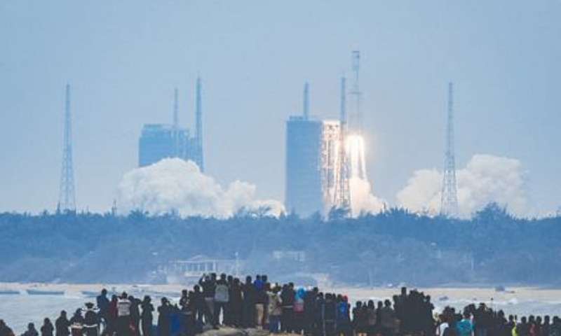 BEIJING: Spectators watch a Long March-8 rocket lifting off from the Wenchang launch centre in southern China's Hainan province on Tuesday.—AFP