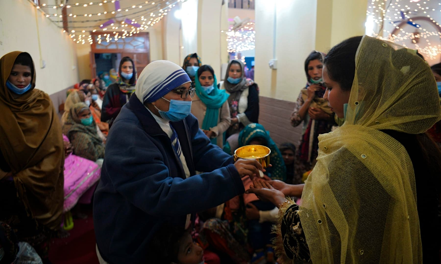A nun wearing a facemask distributes holy communion to devotees during Christmas prayers at the Holy Family Catholic Church in Rawalpindi on December 25. — AFP