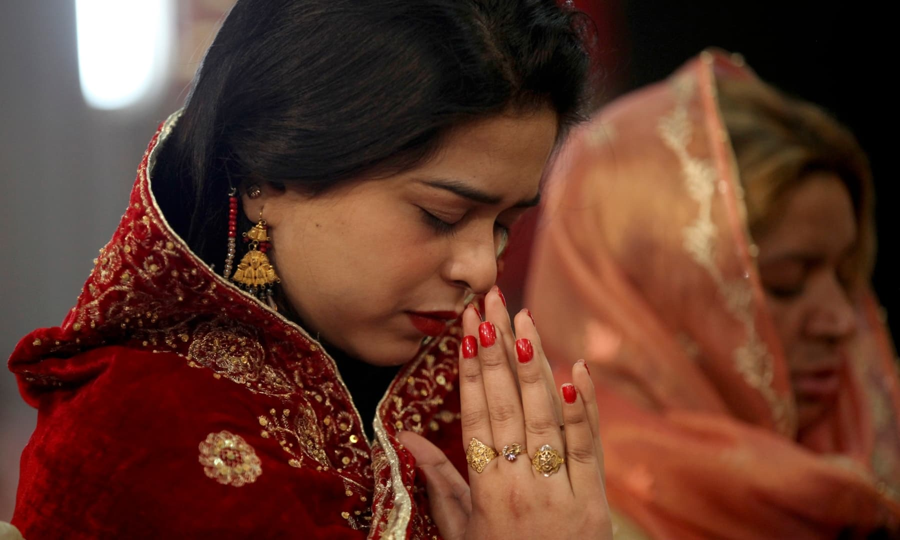 A Christian woman prays during Christmas mass in Sacred Heart Cathedral in Lahore. — AP