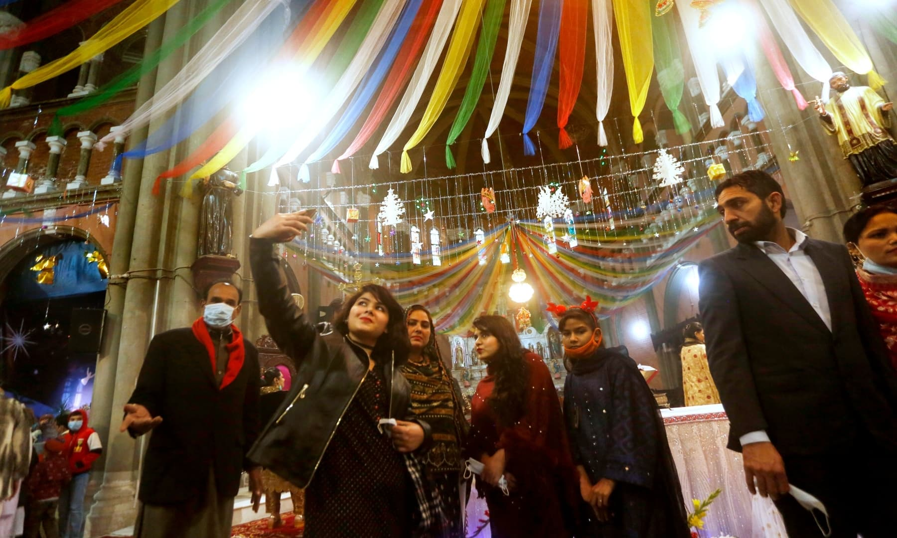 A girl takes a selfie after attending a Christmas mass in Sacred Heart Cathedral in Lahore, Friday. — AP