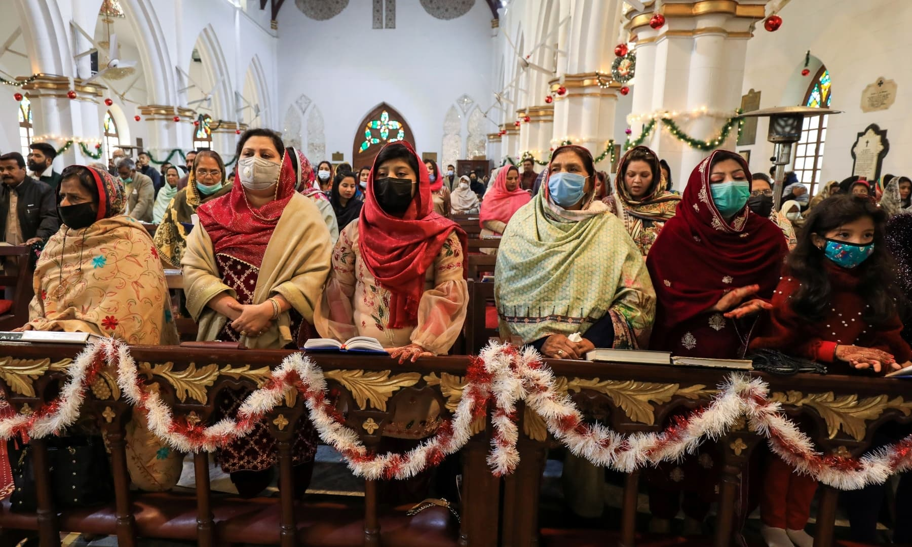 People wearing protective masks attend a Christmas service at St. John's Cathedral in Peshawar, December 25, 2020. — Reuters