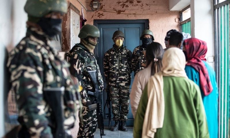 Soldiers stand guard as Kashmiris wait outside a polling booth to cast their votes during the first phase of District Development Councils election on the outskirts of Srinagar, Indian-occupied Kashmir, Saturday, Nov 28. — AP