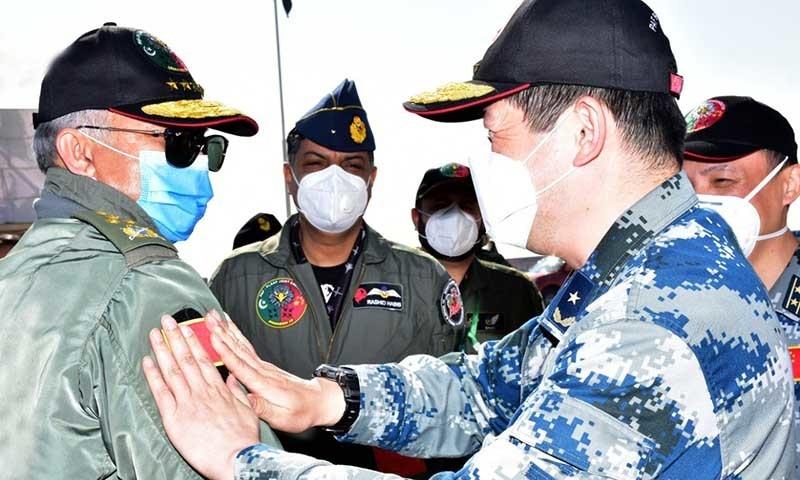 ایئر چیف مارشل مجاہد انور کے بازو پر چینی طیارہ اڑانے سے پہلے چینی پرچم لگایا جارہا ہے—تصویر: پی اے ایف
