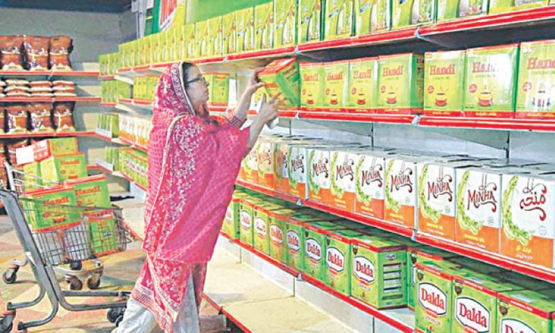 A woman picks up a carton of cooking oil at a store. Increase in ghee and cooking oil prices is forcing many consumers to buy these items on a 'as needed' basis instead of bulk buying as part of monthly grocery.