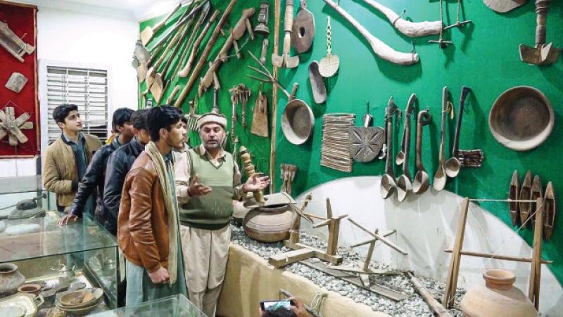 Amir Khaliq briefs visitors at his museum in Salampur village, Swat. — Dawn
