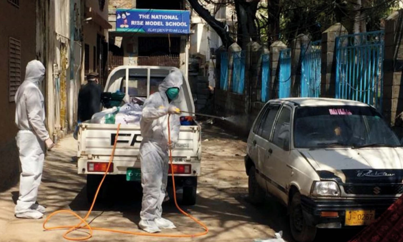 Health workers in Abbottabad spray chlorine water in a street after the death of a coronavirus patient was reported from the area. — APP/File