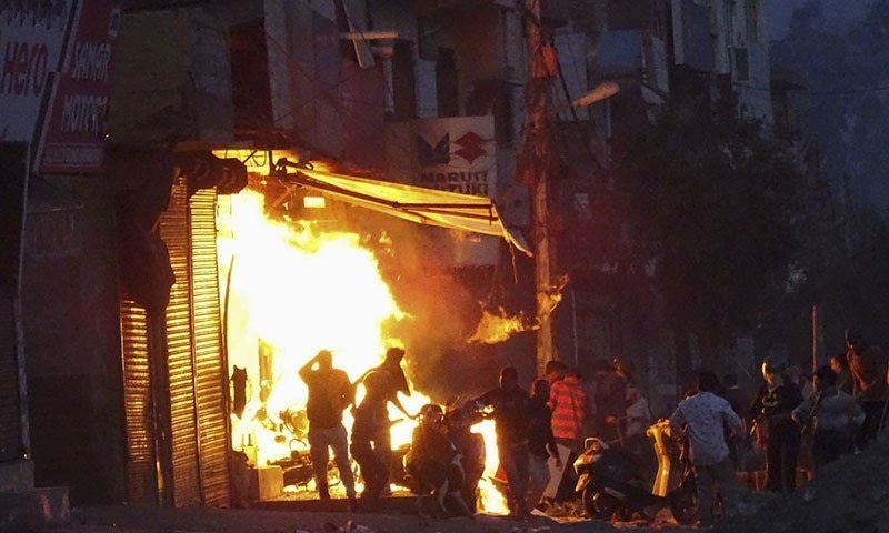 A shop is set on fire during violence between two groups in New Delhi, India, on Feb 26. — AP