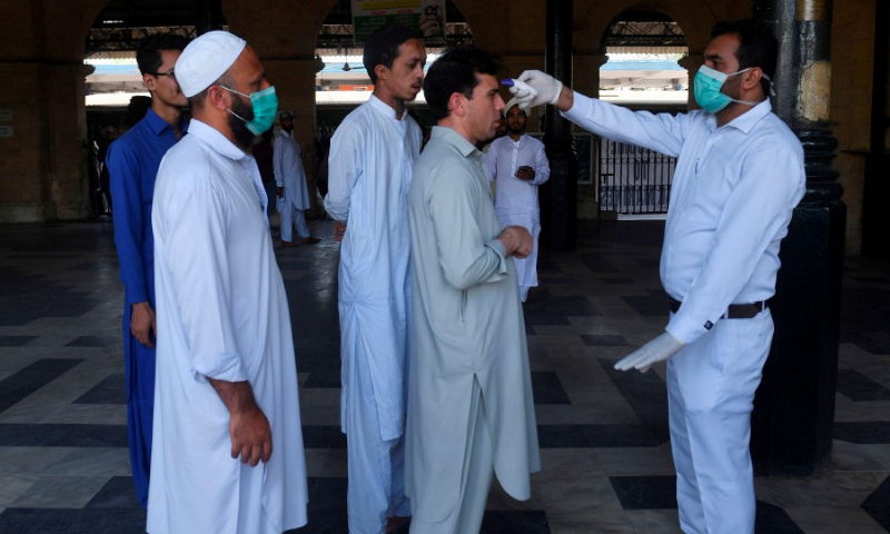 A health official checks the body temperature of a passengers amid concerns over the spread of the COVID-19 novel coronavirus, at Karachi Cantonment railway station in Karachi. — AFP/File