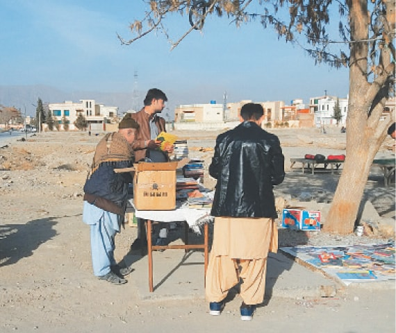 ABDUL Khaliq deals with customers at his 'stall' under a tree in Quetta's Jinnah Town Square.—Photo by writer