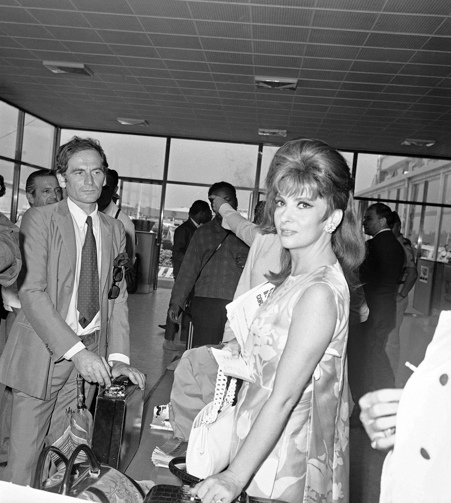 In this Sept7, 1967 file photo, Italy's Gina Lollobrigida and French designer Pierre Cardin arrive at the Venice airport to attend the Venice International Film Festival. — AP