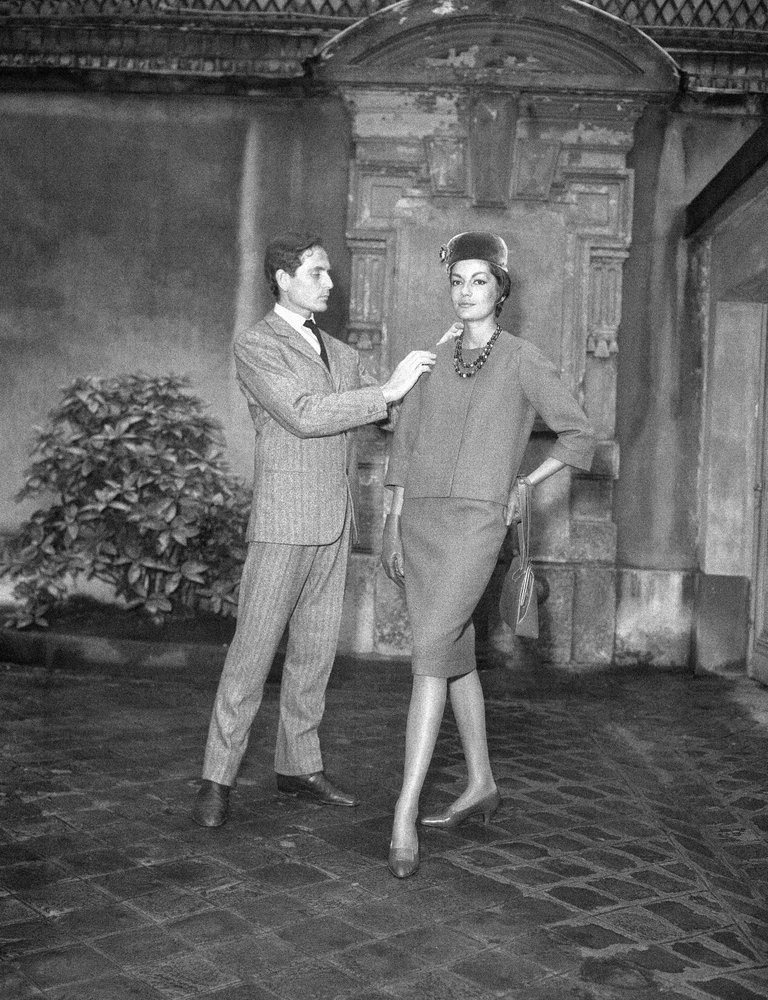In this Sept13, 1960 file photo, Parisian designer Pierre Cardin, with one of his models, shows the new uniform he has created for the hostesses of French television in Paris. — AP