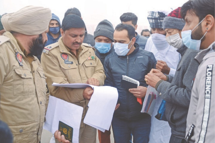 AMRITSAR: Policemen check the travel documents of Pakistani nationals, who were stranded in India following the closure of borders in view of the Covid-19 pandemic, before they were allowed to cross the India-Pakistan border on Tuesday through the Attari-Wagah post, some 35km from here.—AFP