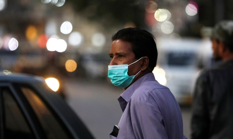 A man wearing a protective mask walks outside a shopping area in Karachi on Dec 29. — Reuters
